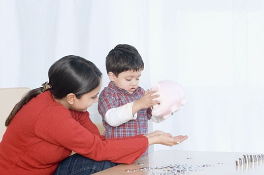 Stock Photo: 1657R-21914 Boy dropping coins from a piggy bank with his mother sitting beside him