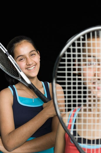Teenage girl holding a badminton racket with her sister : Stock Photo