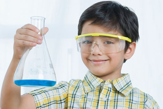 Stock Photo: 1657R-22729 Portrait of a boy holding a conical flask and smiling