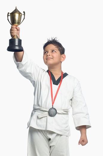 Boy picking up a trophy : Stock Photo
