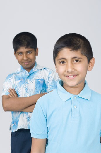 Portrait of a boy smiling and another boy standing in the background with his arms crossed : Stock Photo