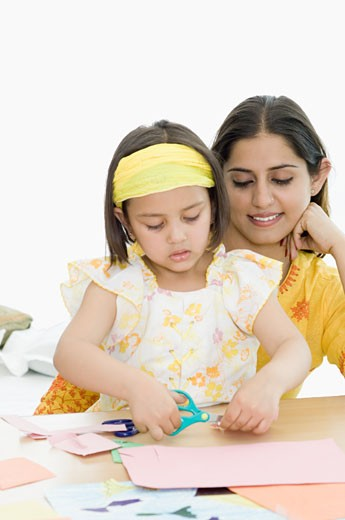 Stock Photo: 1657R-23004 Girl cutting papers with scissors and her mother behind her