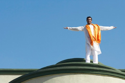 Low angle view of a young man standing on the roof of a building with his arms outstretched : Stock Photo