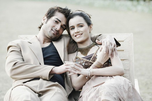Stock Photo: 1657R-23268 Portrait of a young couple sitting on a bench