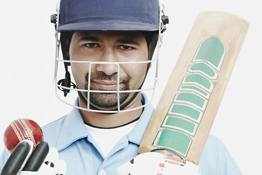 Portrait of a young man holding a cricket bat and a cricket ball : Stock Photo