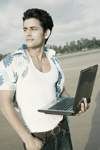 Close-up of a young man standing on the beach and holding a laptop : Stock Photo