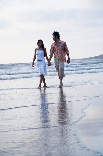 Stock Photo: 1657R-28304 Young couple walking on the beach