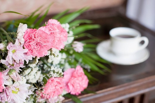 Close-up of flowers with a cup of coffee on a table : Stock Photo