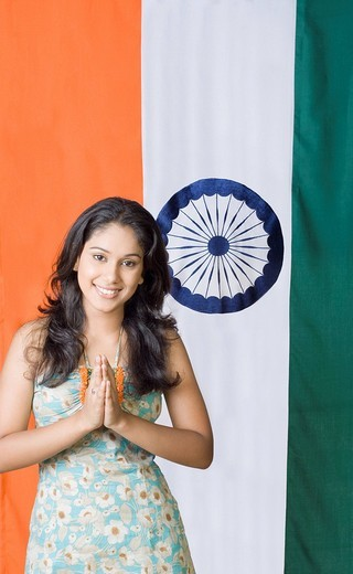 Stock Photo: 1657R-28952 Portrait of a young woman standing in front of an Indian Flag