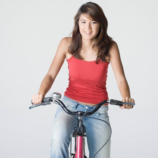 Portrait of a young woman riding a bicycle and smiling : Stock Photo