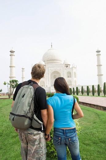 Rear view of a young couple looking at a mausoleum, Taj Mahal, Agra, Uttar Pradesh, India : Stock Photo
