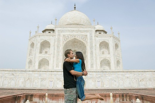 Side profile of a young couple embracing each other in front of a mausoleum, Taj Mahal, Agra, Uttar Pradesh, India : Stock Photo