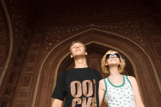 Close-up of a young couple standing and smiling, Taj Mahal, Agra, Uttar Pradesh, India : Stock Photo