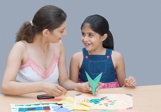 Young woman helping her daughter in drawing : Stock Photo