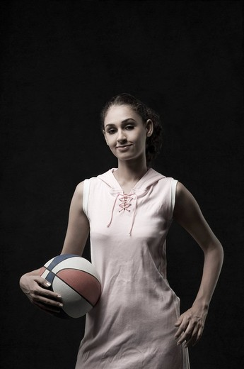 Portrait of a young woman standing and holding a volleyball : Stock Photo