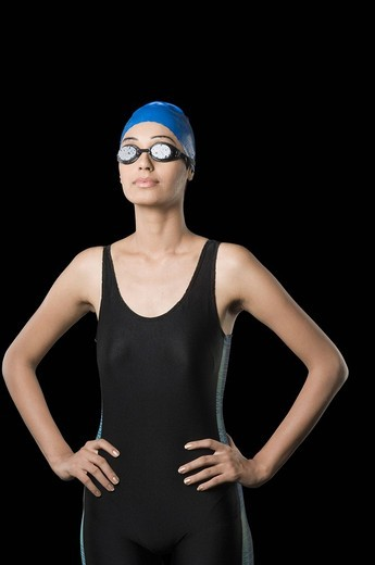 Young woman standing with arms akimbo in swimwear : Stock Photo