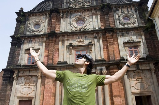 Young man standing in front of a building with his arms outstretched, Goa, India : Stock Photo