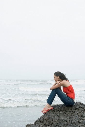 Stock Photo: 1657R-29930 Side profile of a young woman sitting on a rock and looking at the sea