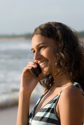 Side profile of a young woman talking on a mobile phone and smiling : Stock Photo