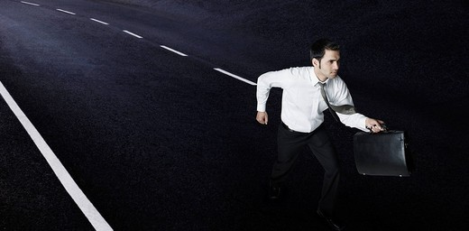 Businessman running on the road : Stock Photo