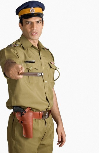 Portrait of a policeman holding a nightstick : Stock Photo