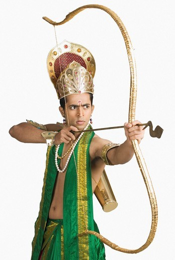 Young man in a character of Arjuna and holding a bow and arrow : Stock Photo