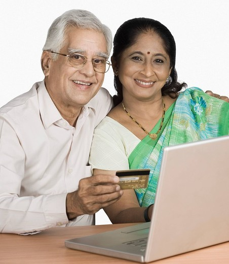 Senior man and a mature woman shopping online : Stock Photo
