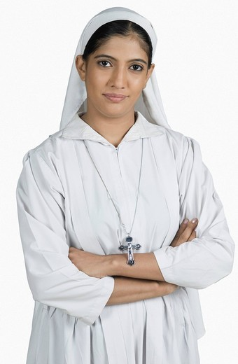 Portrait of a nun standing with her arms crossed : Stock Photo