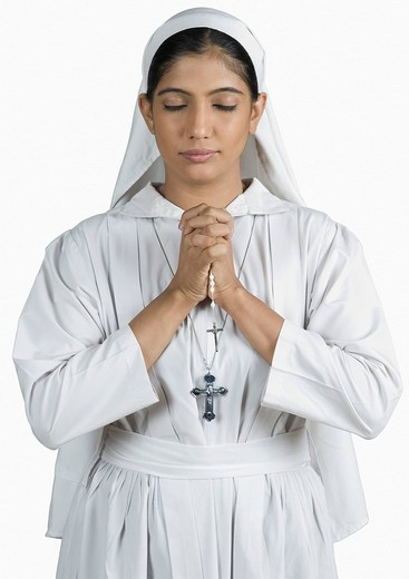 Close_up of a nun standing in the prayer position : Stock Photo