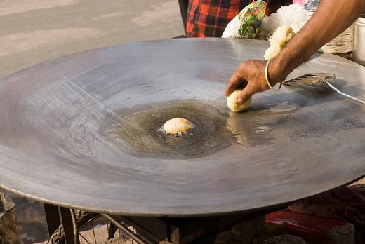 Stock Photo: 1657R-32468 Man frying aloo tikki on a griddle, Delhi, India