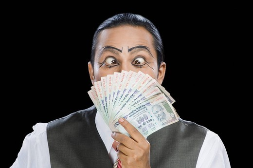 Close_up of a mime holding currency notes : Stock Photo