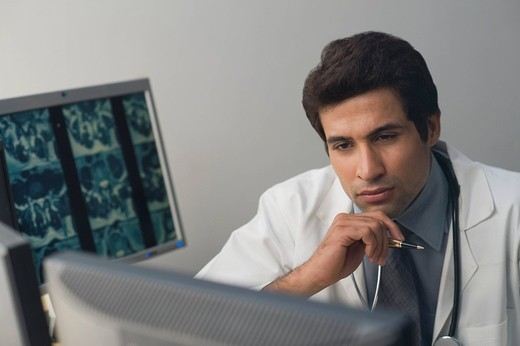 Male doctor examining an X_Ray report : Stock Photo