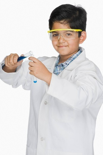 Boy in a lab coat experimenting with test tubes : Stock Photo
