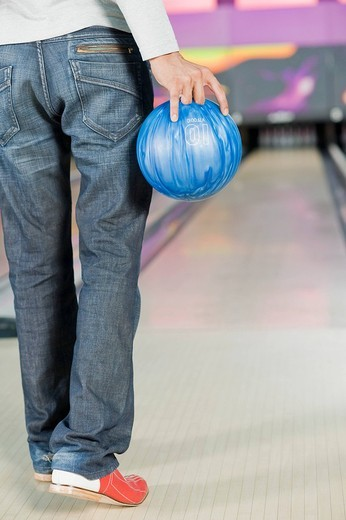 Young man holding a bowling ball in a bowling alley : Stock Photo