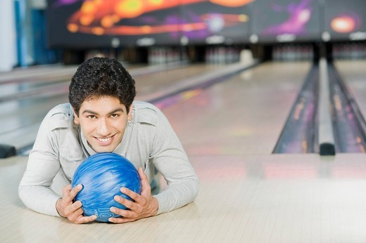 Young man lying with a bowling ball in a bowling alley : Stock Photo
