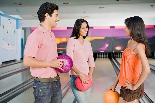 Young couple with their friend holding bowling balls in a bowling alley : Stock Photo