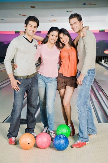 Two young couples with bowling balls in a bowling alley : Stock Photo