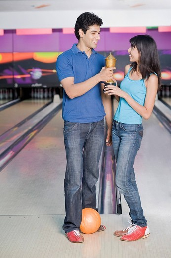 Young couple with a bowling ball and a trophy in a bowling alley : Stock Photo