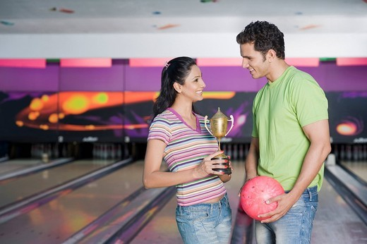 Stock Photo: 1657R-33610 Young couple with a bowling ball and a trophy in a bowling alley