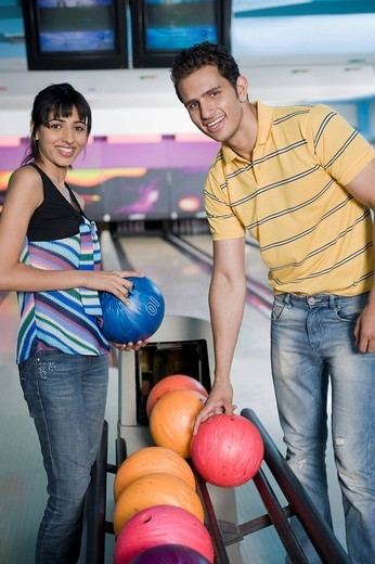 Young couple picking bowling balls and smiling in a bowling alley : Stock Photo