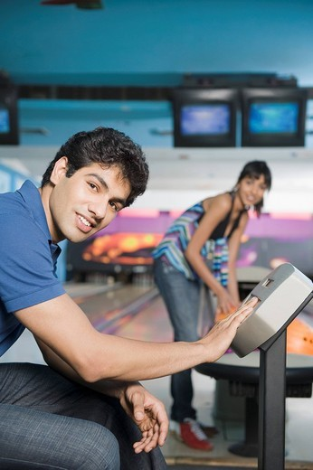 Young man operating the control panel and his friend looking at him in a bowling alley : Stock Photo