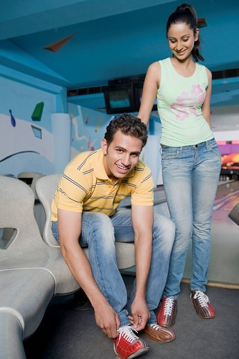 Portrait of a young man tying his shoelace with his girlfriend standing behind him in a bowling alley : Stock Photo