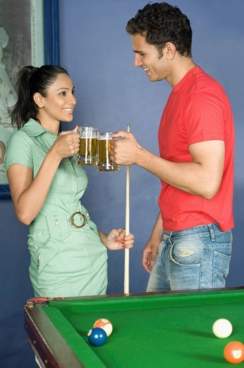 Young couple toasting beer glasses in the pool room : Stock Photo