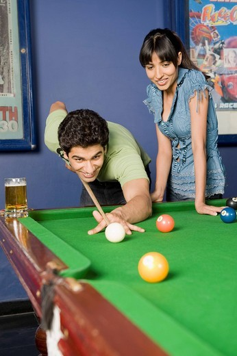 Young man playing pool and a young woman watching his game : Stock Photo