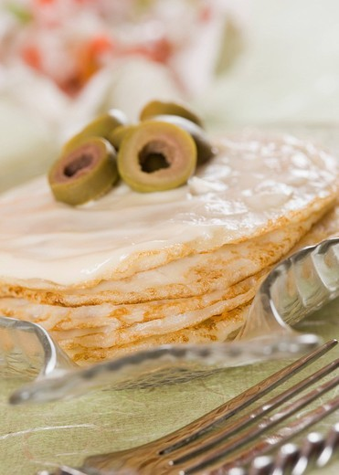 Green olive slices on pancakes on a plate : Stock Photo