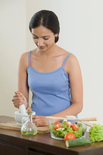 Woman grinding vegetable into mortar and pestle : Stock Photo