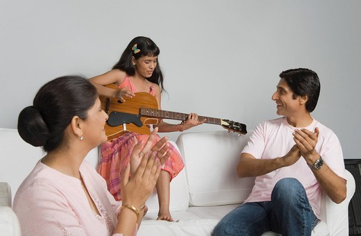 Girl playing a guitar and her parents applauding : Stock Photo