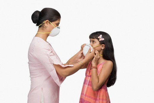 Young woman putting a pollution mask to her daughter : Stock Photo