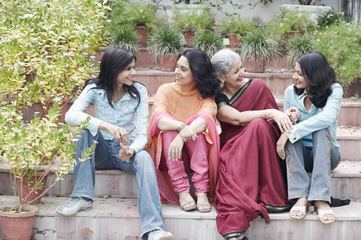Four women sitting on steps together smiling : Stock Photo