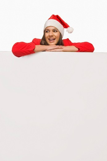 Stock Photo: 1657R-35158 Woman in Santa costume leaning over a white board and smiling